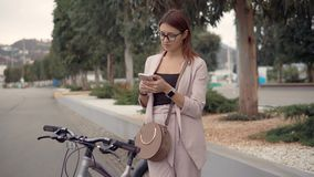 Flicka på en cykel med smartphonen stock video