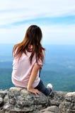 Flicka på en klippa Arkivbild