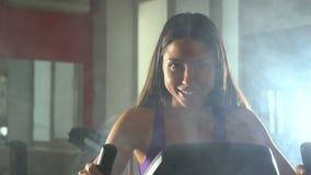 Flicka på en motionscykel långsam rörelse arkivfilmer