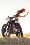 Flicka på en motorcykel Hon är härlig och att posera på en motorcykel på solnedgången royaltyfria foton