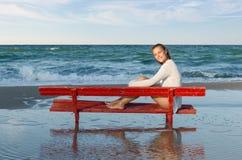 Flicka på en röd bänk Arkivbild