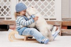 Flicka på en släde med en liten hund Arkivbild