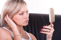 Flicka på en sofa med en spegel royaltyfri foto