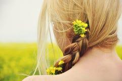 Flicka på en solig dag i blomninggulingfältet Arkivbilder