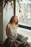 Flicka på fönstret med en kopp kaffe och en tidskrift Arkivfoton