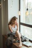 Flicka på fönstret med en kopp kaffe och en tidskrift Royaltyfri Bild