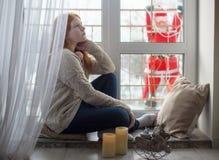 Flicka på fönstret med Santa Claus Fotografering för Bildbyråer