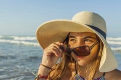 Flicka på för strandsommar för strand den bärande admirien för hatt och för solglasögon Arkivfoto