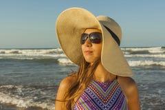 Flicka på för strandsommar för strand den bärande hatten och solglasögon Arkivbilder