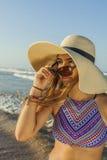 Flicka på för strandsommar för strand den bärande hatten och solglasögon Royaltyfri Bild
