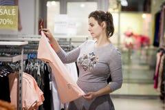 Flicka på försäljningen av modekläder i lager den unga kvinnan shoppar på svarta fredag flickan väljer kläder i trendig boutique fotografering för bildbyråer