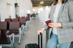 Flicka på flygplatsen med bagage och passet royaltyfria bilder