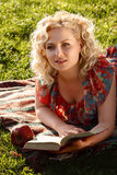 Flicka på gräset med en bok Royaltyfri Bild