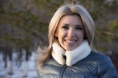 Flicka på grå bakgrund i den utomhus- vintern Fotografering för Bildbyråer