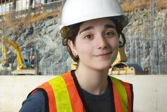 Flicka på konstruktionsplats med den orange västen och vitsäkerhetshatten Arkivfoto