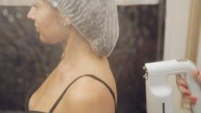 Flicka på kroppögonblicksolbrännan i skönhetsalong stock video