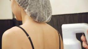 Flicka på kroppögonblicksolbrännan i skönhetsalong arkivfilmer
