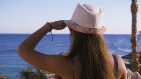 Flicka på kusten som omkring ser på det azura havet lager videofilmer