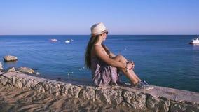 Flicka på kusten som ser till det azura havet arkivfilmer