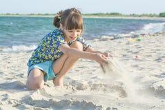 Flicka på kusten som spelar med sand på en bakgrund av havet och vågor arkivbild