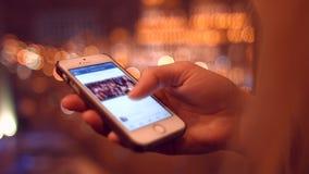 Flicka på mobiltelefonvisningnyheterna på facebook 4K 30fps ProRes stock video