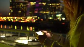 Flicka på natten med en smartphone på internet stock video