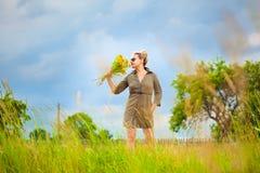 Flicka på naturen med en bukett av blommor i henne hand Arkivbild