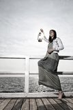 Flicka på pir med fotogenlampan Arkivfoto