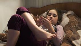 Flicka på säng som spelar på smartphonen stock video