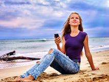 Flicka på sand nära havsappellhjälp vid telefonen royaltyfria bilder