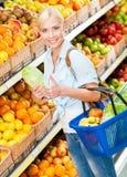 Flicka på shoppinggallerian som väljer grönsaker royaltyfri fotografi