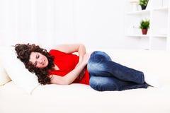 Flicka på sofaen med mageknip royaltyfria foton