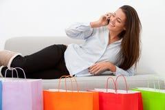 Flicka på soffan med mobil- och shoppingpåsar Arkivfoton