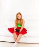 Flicka på soffan som spelar videospel Arkivfoto