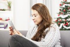 Flicka på soffan som surfar med minnestavlan på jul Arkivbilder