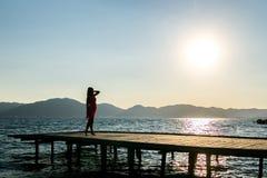 Flicka på solnedgången på pir Royaltyfri Foto