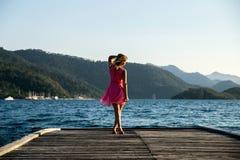 Flicka på solnedgången på pir Arkivbilder