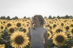 Flicka på solrosfältet Arkivfoto