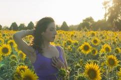 Flicka på solrosfältet Arkivbild