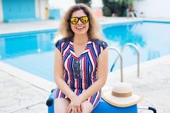 Flicka på sommarferier på bakgrunden av pölen, den klädde randiga klänningen och solglasögon Royaltyfria Foton