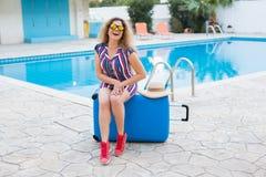 Flicka på sommarferier på bakgrunden av pölen, den klädde randiga klänningen och solglasögon Fotografering för Bildbyråer