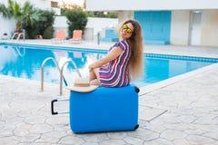 Flicka på sommarferier på bakgrunden av pölen, den klädde randiga klänningen och solglasögon Royaltyfri Bild