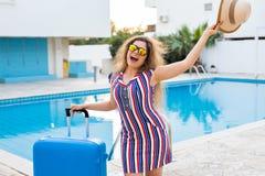 Flicka på sommarferier på bakgrunden av pölen, den klädde randiga klänningen och solglasögon Arkivbilder