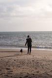 Flicka på stranden med Boston Terrier Arkivbild