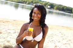 Flicka på stranden med en drink arkivbilder