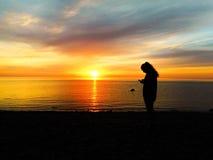 Flicka på stranden på solnedgången Arkivbilder