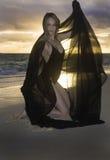 Flicka på stranden på soluppgång Royaltyfri Bild
