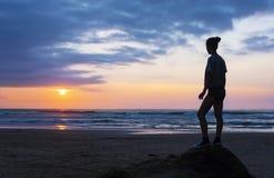 Flicka på stranden på solnedgången med solen över havet Royaltyfria Foton