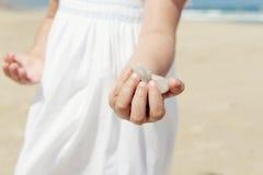 Flicka på strandinnehavstenarna fotografering för bildbyråer