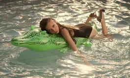 Flicka på uppblåsbar madrasskrokodil i pölen royaltyfria foton